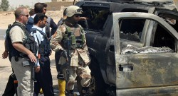 A private security contractor (L) and soldiers look at a destroyed vehicle after an attack near the Iraqi city of Najaf May 18, 2006. Witnesses said a roadside bomb exploded near a convoy of vehicles commonly used by private security firms, killing one Iraqi policeman. REUTERS/Ali Abu Shish - RTR1DHVM